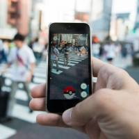 All across Japan people were fixated on their smartphones trying to catch augmented-reality cartoon characters via the 'Pokemon Go' app, which inevitably led to some accidents and lectures on phone etiquette. | BLOOMBERG