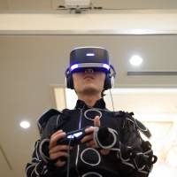 Above: A man plays video games at the Japan VR Summit 2 in Tokyo in November while wearing a Sony PlayStation VR headset and a Synesthesia Suit that was produced by Enhance Games, Rhizomatiks and Keio Media Design. Right: Hon Hai Precision Industry Co. Chairman Terry Gou (center), Vice Chairman Tai Jeng-wu (left) and Sharp President Kozo Takahashi clasp hands at a news conference. | BLOOMBERG