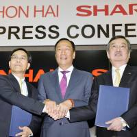Hon Hai Precision Industry Co. Chairman Terry Gou (center), Vice Chairman Tai Jeng-wu (left) and Sharp President Kozo Takahashi clasp hands at a news conference. | KYODO