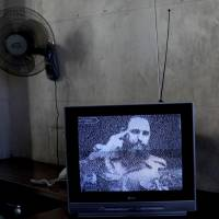 A TV broadcasts black-and-white footage of Fidel Castro at a memorial on the outskirts of Havana.   AP