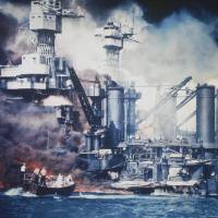 Survivor: A USS West Virginia crew member is rescued from the water after the bombing of Pearl Harbor, Hawaii, on Dec. 7, 1941.  The mast of the USS Tennessee is beyond the burning West Virginia. | AP