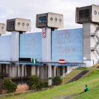 Grass and concrete: A man relaxes near the Iwabuchi Water Gate. The surrounding area is a popular space for cycling, fishing and picnics. | LANCE  HENDERSTEIN