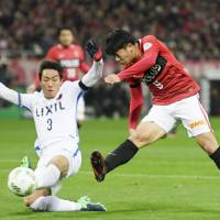 Antlers defender Gen Shoji tries to deflect a shot by Reds' Yuki Muto during the second leg of the J. League Championship final on Saturday at Saitama Stadium. | KYODO