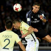 Real Madrid's Cristiano Ronaldo (right) collides with Club America's Pablo Aguilar during Madrid's 2-0 win in their Club World Cup semifinal in Yokohama on Thursday. | AFP-JIJI