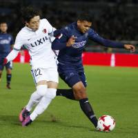 Auckland City's Ryan De Vries (right), and Kashima's Daigo Nishi vie for the ball in the opening match of the Club World Cup on Thursday. | AP