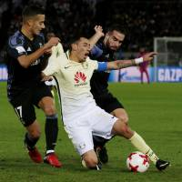 Club America's Rubens Sambueza (center) is tackled by Real Madrid's Lucas Vazquez (left) and Daniel Carvajal on Thursday. | AP