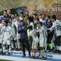 The Real Madrid players celebrate on the podium after winning the Club World Cup on Sunday. | AP