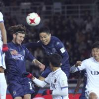 Auckland City's Kim Dae-wook (center), heads the ball to score his club's first goal against the Kashima Antlers during a Club World Cup match on Thursday at Nissan Stadium. | AP
