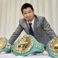 Hozumi Hasegawa poses with his three WBC championship belts during a Friday news conference in Kobe. The 35-year-old boxer announced his retirement. | KYODO