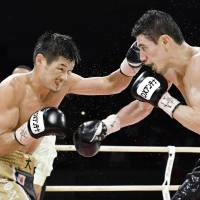 Hozumi Hasegawa (left), seen in a file photo from September during his WBC super bantamweight title fight against Hugo Ruiz of Mexico, captured world titles in three different weight classes. | KYODO