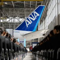 New employees of the ANA Group, parent of All Nippon Airways Co., attend an initiation ceremony at a hangar in Tokyo last April. | BLOOMBERG