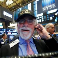A trader works on the floor of the New York Stock Exchange (NYSE) as the Dow Jones Industrial Average passes the 20,000 mark shortly after the opening of the trading session in New York Wednesday. | REUTERS