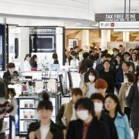 Customers browse a duty-free shop in Tokyo's Ginza district. Kansai Airports has scrapped a plan to open a duty-free shop in central Osaka due to a slowdown in bakugai shopping sprees. | KYODO