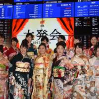 Kimono-clad women pose at the opening of the year's first trading day at the Tokyo Stock Exchange on Wednesday. | SATOKO KAWASAKI