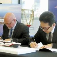 Officials from the Australian and Japanese governments sign a memorandum of understanding in Canberra, Australia, on Wednesday. | KYODO