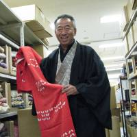 Kenichi Nakamura, president of Tokyo Yamaki Co., which runs Tansuya, Japan's largest used kimono chain, holds one of the garments at the company's Tokyo headquarters on Dec. 14. | KYODO