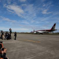 Members of the media look on as Mitsubishi Aircraft Corp.'s Mitsubishi Regional Jet touches down following its first flight at Nagoya airport in Aichi Prefecture on Nov. 11, 2015. | BLOOMBERG