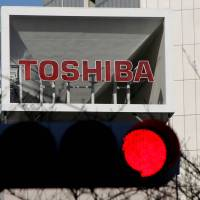 The logo of Toshiba Corp is seen at its Tokyo headquarters on Friday, when the company announced that it will spin off its cash-cow chip business at the end of March. | REUTERS