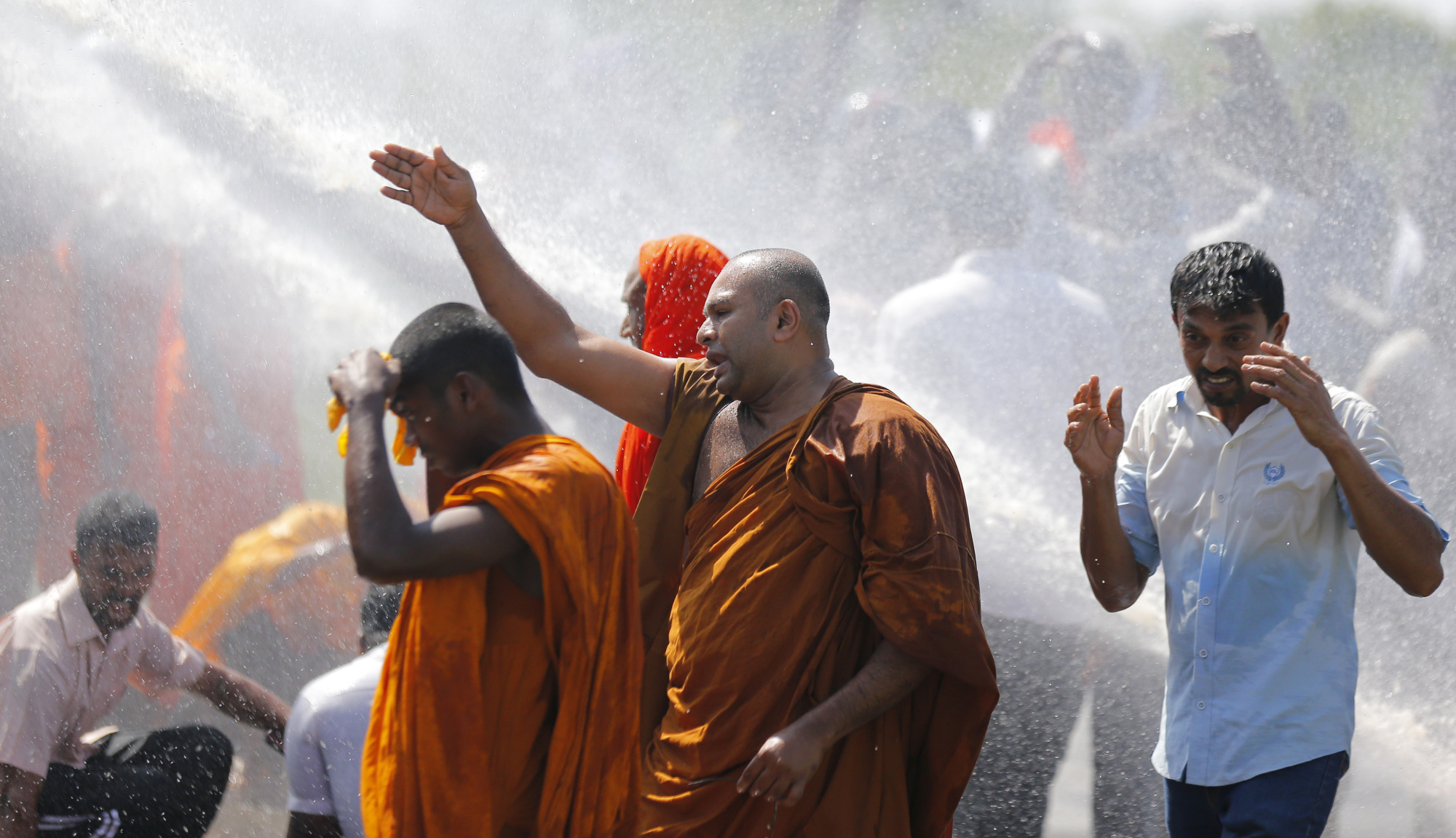 Sri Lankan police use water cannon to disperse monks and villagers protesting outside the inauguration ceremony of an industrial zone in Mirijjawila village in Ambalantota, Sri Lanka, Saturday.   AP