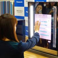Panasonic Corp. engineer Masayo Fuchigami demonstrates the Snow Beauty Mirror on Dec. 1 in Tokyo. | SHUSUKE MURAI