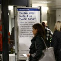 Passengers pass through ticket turnstiles at Waterloo Underground Station next to a notice giving details of a strike involving London Underground workers, in central London Sunday. The walkout on the Tube is part of a wave of strikes hitting British rail and air passengers at the start of 2017. | REUTERS