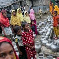 Rohingya women and children wait to collect water at the Leda camp, an unregistered camp for Rohingya in Teknaf, near Cox's Bazar in southern Bangladesh, on Dec. 3. | AP