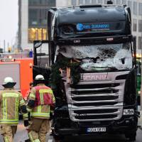 This Dec. 20 photo shows the truck at the scene where it crashed into a Christmas market near the Kaiser-Wilhelm-Gedaechtniskirche (Kaiser Wilhelm Memorial Church) in Berlin. German police in Berlin on Tuesday searched a home of asylum seekers where a 26-year-old Tunisian, who had contact with Anis Amri, lives and a second search took place in an apartment in Berlin housing a former roommate of the alleged perpetrator of the attack that killed 12 people. | AFP-JIJI