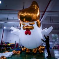 Workers inflate a giant chicken balloon resembling U.S. President-elect Donald Trump at a factory in Jiaxing, China, on Friday. | AFP-JIJI