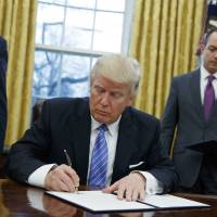 President Donald Trump signs an executive order to withdraw the U.S. from the 12-nation Trans-Pacific Partnership trade pact, which had been agreed to under the Obama administration, in the Oval Office of the White House in Washington on Jan. 23. | AP