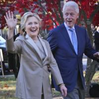 Hillary Clinton and her husband, former President Bill Clinton, greet supporters after voting in Chappaqua, New York, on Nov. 8. | AP