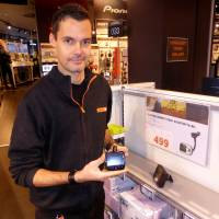 Expert City electronics shop worker Ino Andre Nilsen shows an adapter that can be plugged into a car FM radio in Oslo on Wednesday. | REUTERS