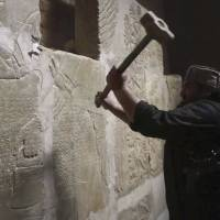 An Islamic State militant takes a sledgehammer to a stone carving at the ancient site of Nimrud near Mosul, Iraq, in this image from video put online by the IS in April 2015. | AP