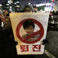 A protester with a defaced portrait of impeached South Korean President Park Geun-hye marches toward the presidential Blue House during a candlelight vigil calling for her to step down in Seoul on Saturday. | AP
