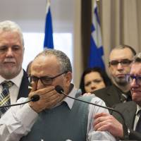 Mohamed Labidi, the vice president of the mosque where an attack happened, is comforted by Quebec Premier Philippe Couillard (left) and Quebec City Mayor Regis Labeaume during a news conference Monday about the fatal shooting at Quebec Islamic Cultural Centre on Sunday. Prime Minister Justin Trudeau and Couillard both characterized the attack at the mosque during evening prayers as a terrorist act. | JACQUES BOISSINOT / THE CANADIAN PRESS VIA AP