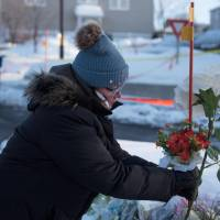 A woman places flowers at a makeshift memorial near the Islamic Cultural Center in Quebec City on Monday. Gunmen stormed into the mosque during evening prayers Sunday and opened fire on dozens of worshippers, killing six and wounding eight in what Canadian Prime Minister Justin Trudeau condemned as a 'terrorist attack.' | AFP-JIJI