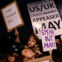 Demonstrators hold placards in London on Monday during a protest against U.S. President Donald Trump's controversial travel ban. | REUTERS