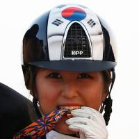 Chung Yoo-ra, formerly known as Chung Yoo-yeon, is the daughter of the woman at the center of South Korea's current huge political scandal. She is biting her gold medal after winning an equestrian competition at the Dream Park Equestrian Venue during the 17th Asian Games in Incheon in September 2014. | REUTERS
