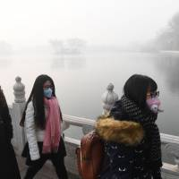 Chinese women wear masks on a heavily polluted day in Beijing on Sunday. China's capital city started the year under a heavy blanket of grey smog, with a concentration of toxic particles 20 times higher than the maximal level recommended by the World Health Organization, as a new pollution cloud was — again — striking the country. | AFP-JIJI
