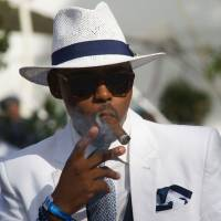 A man smokes a cigar at the L'Ormarins Queen's Plate horse racing event in Cape Town on Saturday. | AFP-JIJI