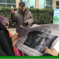 A Chinese man holds up a newspaper with a front page photo of U.S. President-elect Donald Trump and a headline that reads 'Outsider counterattack' in Beijing on Nov. 10. | AP