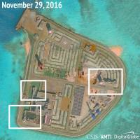 A satellite image shows what appears to be anti-aircraft guns and close-in weapons systems on Johnson Reef, a Chinese-held artificial island in the South China Sea, in this image released last month. | REUTERS