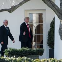 U.S. President Donald Trump gives a thumbs up as he walks to the Oval Office with Vice President Mike Pence after a visit to the Department of Homeland Security at the White House in Washington Wednesday. | AFP-JIJI