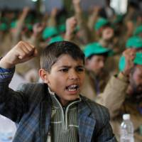 A boy shouts slogans next to injured pro-Houthi fighters, during a rally held to honor those injured or maimed while fighting in Houthi ranks in Sanaa Sunday. | REUTERS