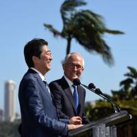 Prime Ministers Shinzo Abe and Malcolm Turnbull speak at a news conference Saturday.   AFP-JIJI