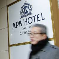 A man walks past the entrance of an Apa Hotel in Tokyo on Jan. 18. | AP