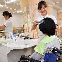 Vietnamese student Vu Thi Thu Trang trains as a nursing care worker at the Japan Welfare Education College in Tokyo on Dec. 22. | KYODO