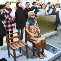 Members of a civic group hold a news conference after erecting a 'comfort women' statue in front of the Japanese Consulate in Busan on Dec. 30. | KYODO