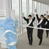 Men celebrating Coming-of-Age Day climb to the top floor of the 60-story Abeno Harukas building in Osaka on Monday. | KYODO