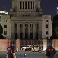 Police officers investigate a car Saturday night that rammed into a police vehicle in front of the Diet.   KYODO
