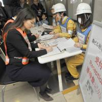 Employees of Mori Building Co. take part in a disaster drill held in three languages at the Roppongi Hills commercial complex in Tokyo on Tuesday. | YOSHIAKI MIURA